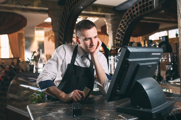 Concepto de pequeñas empresas, personas y servicios: hombre feliz o camarero en delantal en el mostrador con caja trabajando en el bar o cafetería