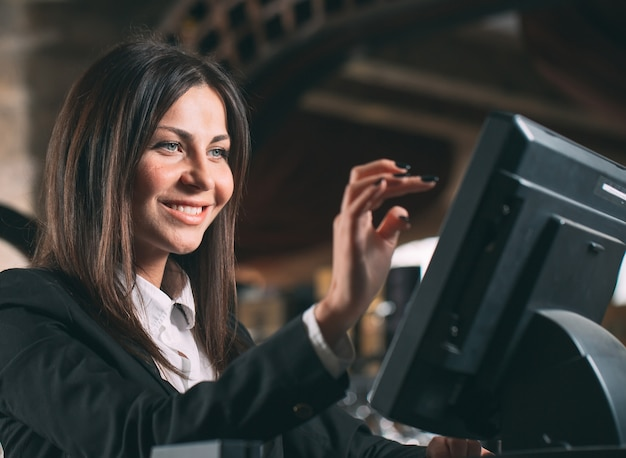 Concepto de pequeñas empresas, personas y servicios: mujer feliz o camarero o gerente en delantal en el mostrador con caja trabajando en el bar o cafetería