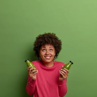 Concepto de pérdida de peso y alimentación limpia. alegre y complacida mujer de piel oscura con corte de pelo afro concentrado arriba, sostiene un batido de espinacas, vestida con un jersey rosa. bebida detox. comida ecológica saludable
