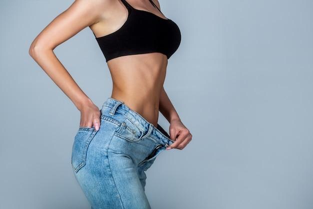 Concepto de pérdida de peso. mujer delgada en pantalones grandes, conceptos de pérdida de peso. chica delgada con pantalones de gran tamaño.