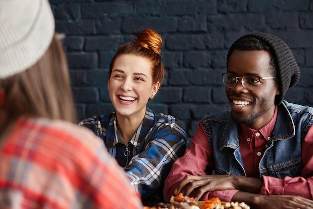 Concepto de personas, amistad y ocio. feliz pareja interracial divirtiéndose en la cafetería moderna, hablando con su amiga y riendo alegremente