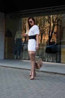Concepto de personas, belleza, moda, estilo de vida y color - hermosa mujer joven con una rodilla. retrato de estilo callejero de una chica elegante con botas de arpillera marrón recta larga.