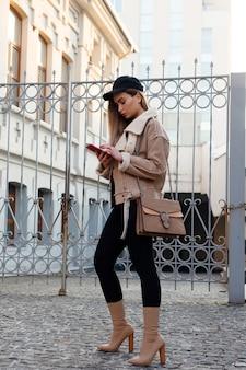 Concepto de personas, belleza, moda, estilo de vida y color - retrato de cuerpo entero al aire libre de joven hermosa niña sonriente feliz posando en la calle. modelo mirando a cámara. chica enviando mensajes de texto en el teléfono inteligente
