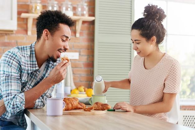 Concepto de personas, cocina y degustación. pareja familiar almuerza en una acogedora cocina: hombre barbudo de piel oscura come delicioso croissant dulce
