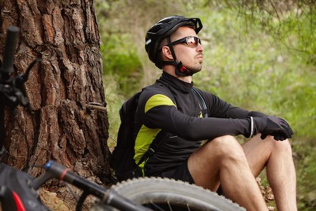 Concepto de personas, deportes, naturaleza y ocio. motociclista caucásico despreocupado relajado en ropa de ciclismo y equipo de protección con un pequeño descanso durante el entrenamiento matutino, con su bicicleta eléctrica acostada cerca de él
