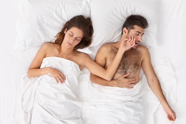 Concepto de personas, descanso y sueño. pareja familiar relajada duerme tranquilamente en una cama cómoda, ve sueños agradables, la mujer extiende la mano sobre su marido, tiene un día de descanso, no quiere despertarse muy temprano.