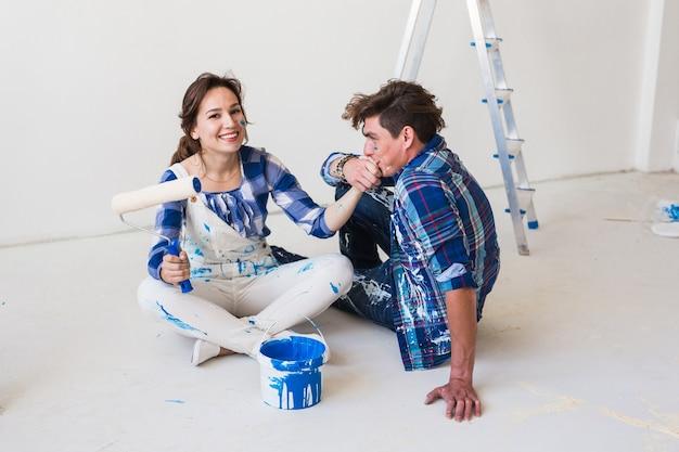 Concepto de personas e interiores - pareja joven sentada en el suelo blanco