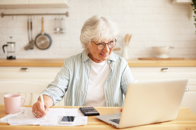 Concepto de personas, edad, tecnología y ocupación. imagen interior de una atractiva mujer jubilada de pelo gris sonriente usando una computadora portátil para el trabajo remoto, sentada en la cocina con papeles, ganando dinero en línea