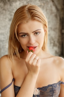 Concepto de personas, emociones, natural, comida, belleza y estilo de vida - sexy rubia con fresas, chica con baya mira a la cámara. mujer joven seductora y sensual