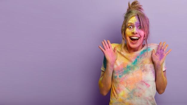 Concepto de personas, emociones y vacaciones. una mujer europea feliz y emotiva levanta las palmas de la felicidad, no puede evitar los sentimientos positivos, impresionado por la celebración del festival de los colores de holi en el extranjero