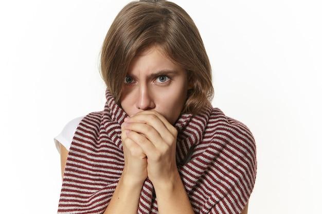 Concepto de personas, enfermedad y salud. primer plano de una mujer caucásica joven frustrada molesta que se siente fría, con una bufanda grande alrededor del cuello y los hombros, respirando con las manos para calentar