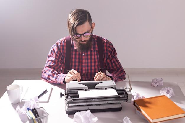 Concepto de personas, escritor y hipster - joven escritor elegante que trabaja en la máquina de escribir