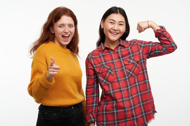 Concepto de personas y estilo de vida. dos niñas felices vestidas con suéter amarillo y camisa a cuadros. apuntándote con una sonrisa y un amigo muestra bíceps. aislado sobre pared blanca