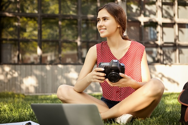 Concepto de personas y estilo de vida. foto de fotógrafa profesional con ropa elegante sosteniendo una cámara dslr sentada en el césped frente a una computadora portátil, retocando fotos de la sesión de fotos de verano
