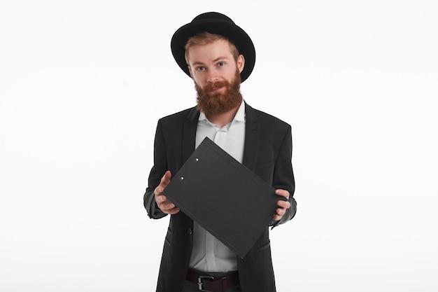 Concepto de personas, estilo de vida y moda. retrato aislado de guapo joven pelirrojo caucásico con barba posando, vestido con traje negro y sombrero, sosteniendo el portapapeles y sonriendo