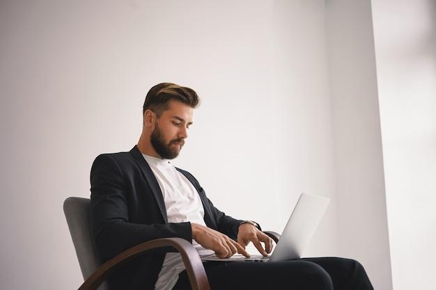 Concepto de personas, estilo de vida moderno, negocios y gadgets. disparo aislado de apuesto joven empresario con barba recortada y peinado elegante usando una computadora portátil genérica, comunicándose con socios en línea