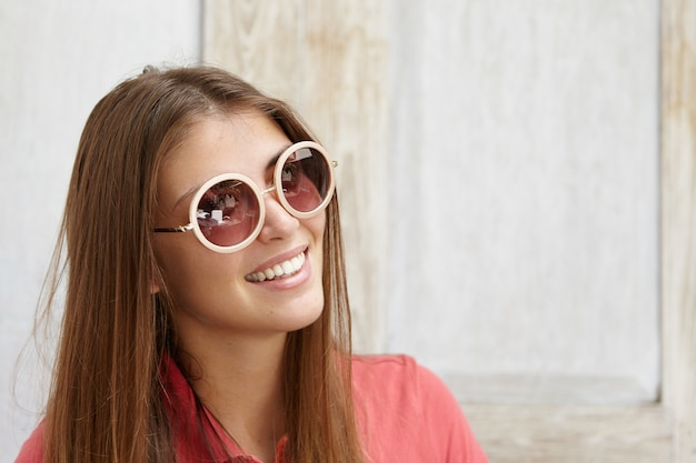 Concepto de personas y estilo de vida. retrato de hermosa joven elegante con piel limpia y sonrisa encantadora con tonos redondos