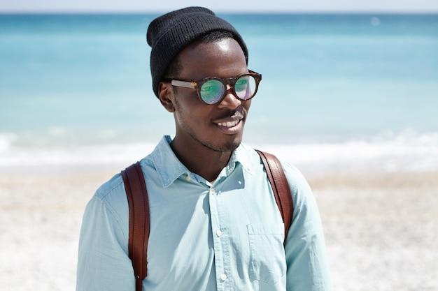 Concepto de personas, estilo de vida, viajes, aventura, vacaciones y turismo. turista europeo negro de moda en ropa de moda que se relaja en la playa en un día soleado de verano, caminando solo por la orilla del mar