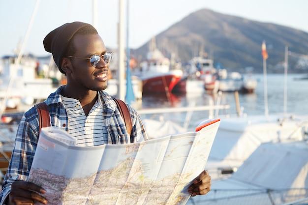 Concepto de personas, estilo de vida, viajes y turismo. guapo joven turista afroamericano de moda vistiendo gafas de sol, sombrero y mochila estudiando el mapa de papel durante sus vacaciones en la ciudad europea