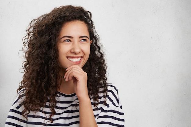 Concepto de personas, felicidad y belleza. mujer morena con amplia sonrisa mira con alegría a un lado, tiene expresión feliz