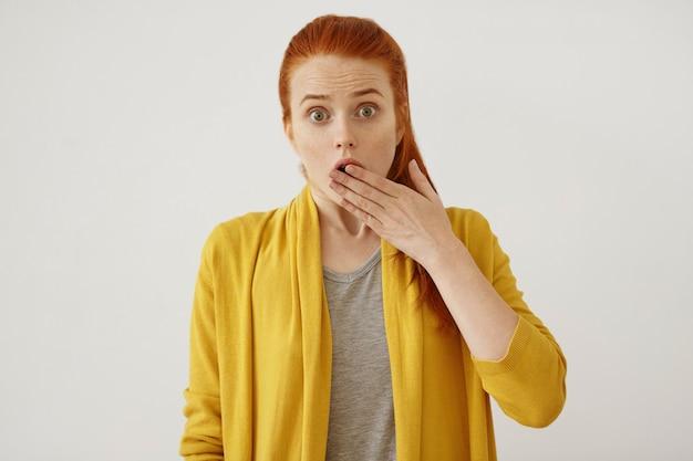 Concepto de personas, lenguaje corporal y expresiones faciales. hermosa pelirroja hembra cubriendo la boca con la mano