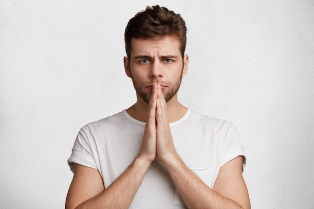Concepto de personas y lenguaje corporal. hermoso macho joven serio mantiene las palmas juntas, cree en la buena suerte antes de un evento importante en la vida,