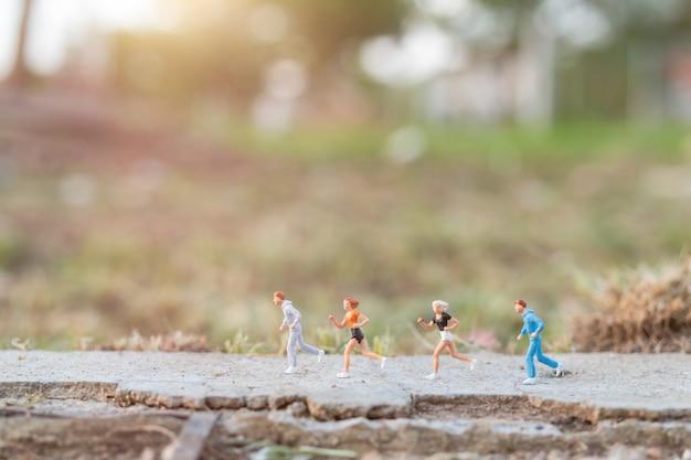 Concepto de personas en miniatura con correr en la carretera