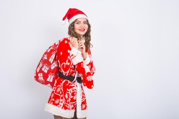 Concepto de personas, navidad y vacaciones - mujer joven en traje de santa claus con bolsa con regalos en la pared blanca con espacio de copia.