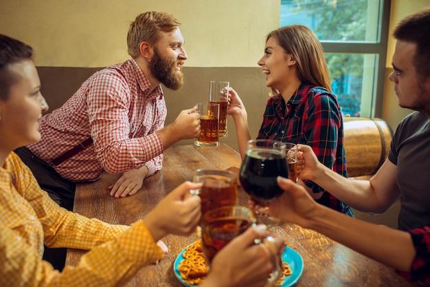 El concepto de personas, ocio, amistad y comunicación: amigos felices bebiendo cerveza, hablando y tintineando vasos en el bar o pub y haciendo fotos autofotos por teléfono móvil.