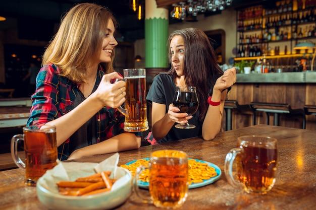 Concepto de personas, ocio, amistad y comunicación: amigos felices bebiendo cerveza, hablando y tintineando vasos en el bar o pub