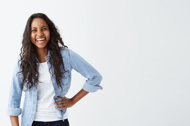 Concepto de personas, ocio y estilo de vida. atractiva joven afroamericana con cabello largo y ondulado, vestida con ropa elegante, sonriendo ampliamente, riéndose alegremente de la broma de alguien, divirtiéndose en el interior.