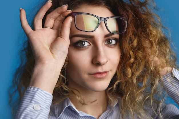 Concepto de personas, óptica, estilo, gafas y moda. retrato de mujer europea joven atractiva con cabello ondulado mirando con sonrisa encantadora, levantando sus anteojos rectangulares de moda
