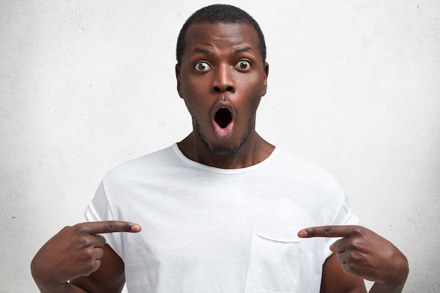 Concepto de personas, publicidad y expresiones faciales. hombre joven atractivo de piel oscura indica en el espacio de copia en blanco de su camiseta casual