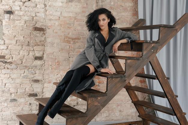 Concepto de personas, raza, etnia y moda - modelo de belleza negro posando en botas altas. mujer en impermeable gris y peinado afro