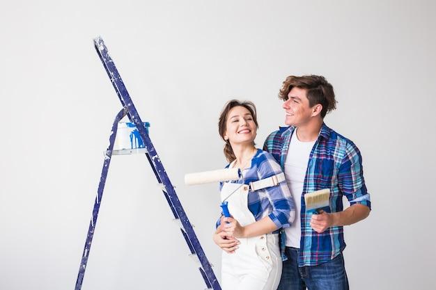 Concepto de personas, redecoración y reparación - encantadora pareja joven haciendo renovación en apartamento nuevo