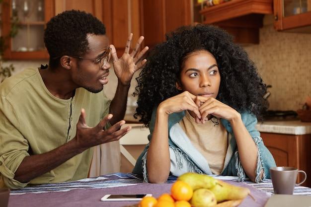 Concepto de personas y relaciones. pareja afroamericana discutiendo en la cocina: hombre con gafas haciendo un gesto de ira y desesperación, gritando a su hermosa novia infeliz que lo ignora por completo