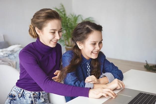 Concepto de personas, relaciones, tecnología, diversión y ocio. dos hermanas alegres jugando videojuegos usando laptop en casa.