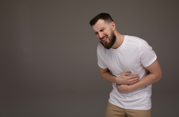 Concepto de personas, salud y problemas. hombre barbudo infeliz que sufre de dolor de estómago sobre fondo gris