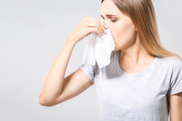 Concepto de personas, salud, rinitis, resfriado y alergia - mujer infeliz con servilleta de papel que sopla la nariz
