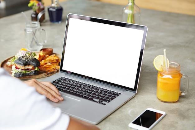 Concepto de personas, tecnología, comunicación y ocio. vista trasera recortada de un hombre joven con una camiseta blanca navegando por internet, revisando las noticias a través de las redes sociales