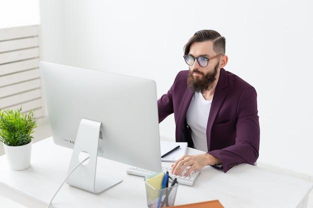 Concepto de personas y tecnología guapo con barba trabajando en la computadora