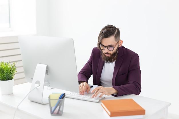 Concepto de personas y tecnología hombre atractivo con barba trabajando en la computadora