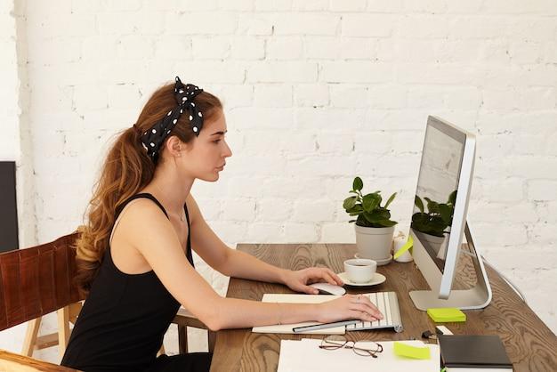 Concepto de personas, tecnología moderna, trabajo, ocupación, profesión, negocios y educación. grave empresaria concentrada trabajando desde casa, sentada en su lugar de trabajo y escribiendo con el teclado en la computadora