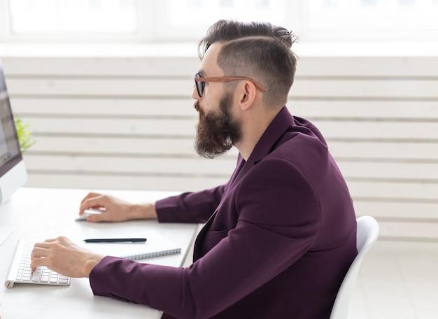 Concepto de personas y tecnología vista lateral retrato de hombre guapo vestido con chaqueta púrpura trabajando en