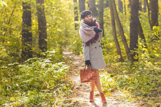 Concepto de personas, temporada y naturaleza - mujer joven caminando en el parque de otoño.