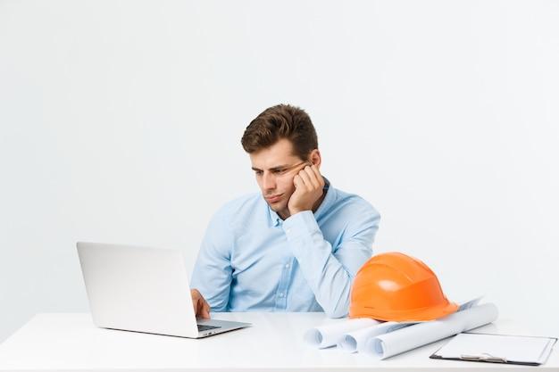 Concepto de personas, trabajo, cansancio y exceso de trabajo. ingeniero de sexo masculino soñoliento aburrido que trabaja hasta tarde.