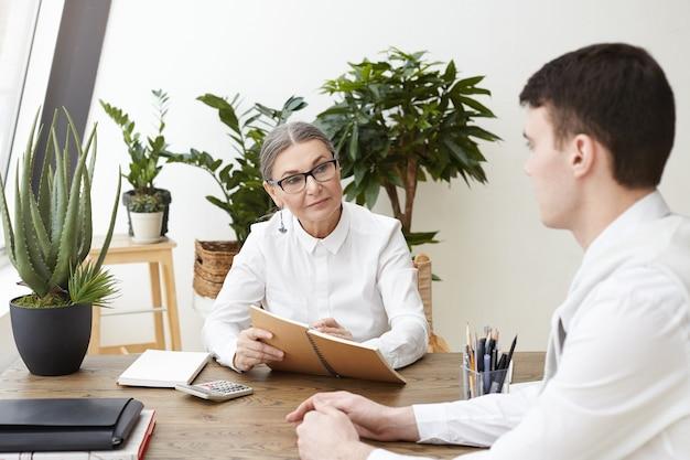 Concepto de personas, trabajo, carrera y contratación. elegante especialista en recursos humanos de 50 años sentada en el escritorio y escribiendo información en un cuaderno mientras entrevista al candidato masculino