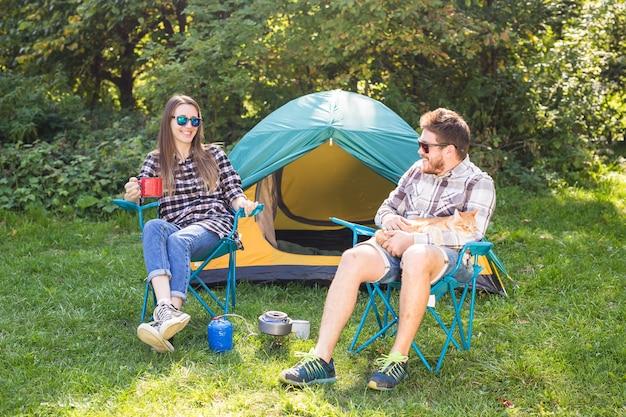 Concepto de personas, turismo y naturaleza: pareja divirtiéndose en un viaje de campamento y jugando con el gato