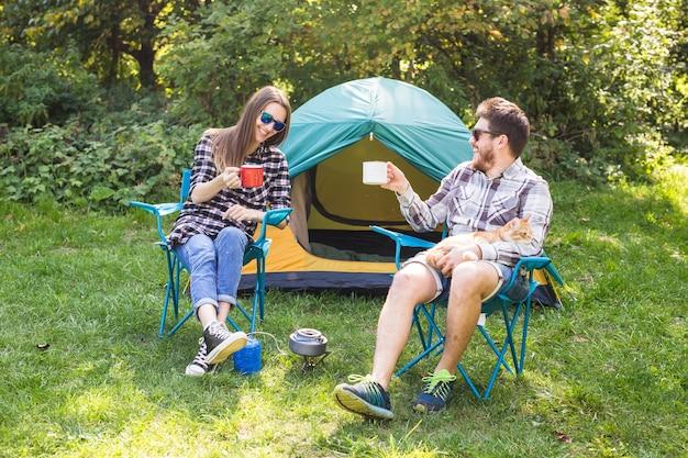 Concepto de personas, turismo y naturaleza - pareja divirtiéndose en viaje de campamento