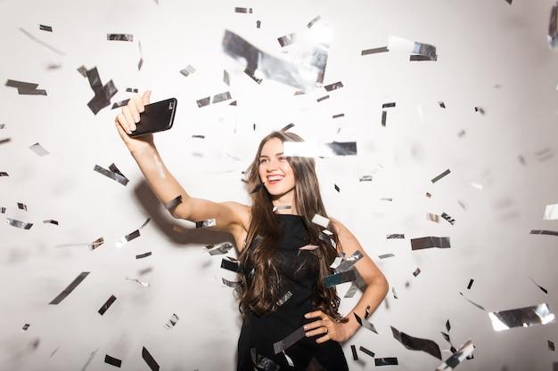 Concepto de personas, vacaciones, emoción y glamour - feliz joven o adolescente en disfraces con lentejuelas y confeti en la fiesta y hacer selfie